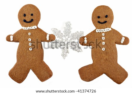 Two homemade gingerbread man cookies holding a silver snowflake, on a white background with copy space.