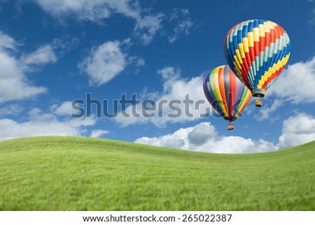 Two Hot Air Balloons Up In The Beautiful Blue Sky With Grass Field Below.