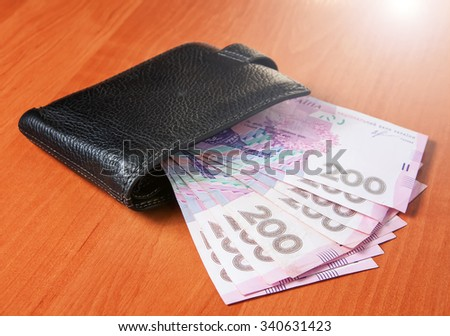 Two hundred Ukrainian hryvnia banknotes in black purse.