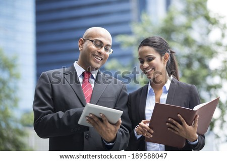 Two Indian business people with digital tablet in a modern urban setting.