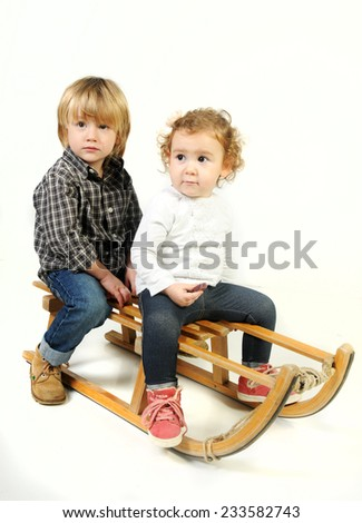 two infant blond kids seating on a vintage wooden sledge Christmas background isolated on white