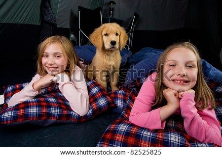 two kids and a puppy camping in a tent with sleeping bags.