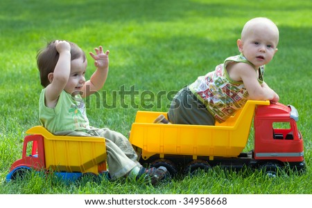 two kids are playing with toy trucks in the park