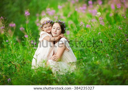 Two kids sit on meadow. Children hugging. Girls in pink dresses in summer on nature. Tenderness and care of a loved one.