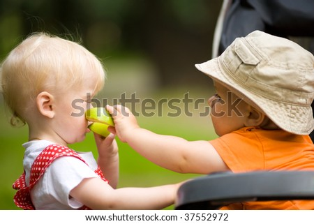 Two kids with apples outdoors looking after each other