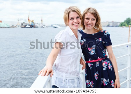 Two ladies on ship deck together with copyspace