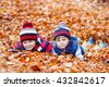 Two little brothers boys lying in autumn leaves in colorful clothing. Happy siblings kids having fun in autumn forest or park on warm fall day. With hats and scarfs - stock photo