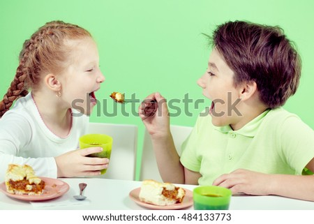 Two little children eating pie and drinking tea