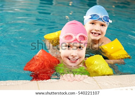 Two little children learning to swim at public swimming pool