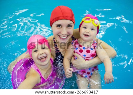 Two little girl  with   mother in  swimming pool