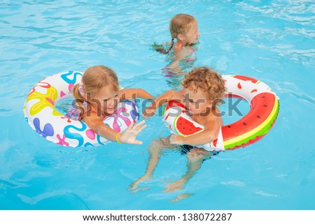 Stock photo two little girls and little boy playing in the pool