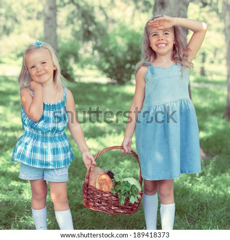 Two little girls carrying basket with organic food for picnic, outdoors. Retro filter photo