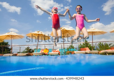 Two little girls jumping in the pool