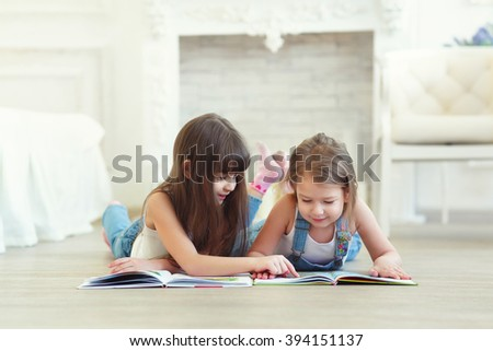 two little girls sisters reading