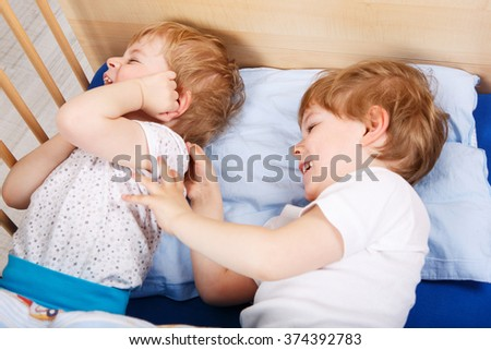 Two little toddler boys having fun and fighting together in bed before sleeping, indoors. Kid boys, little twins in love.