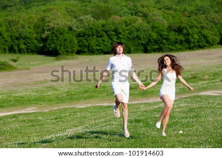 Two lovers playing on the grass meadow