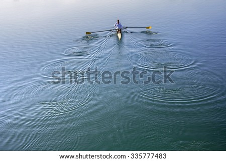 Two Man in a boat, rowing on the tranquil lake