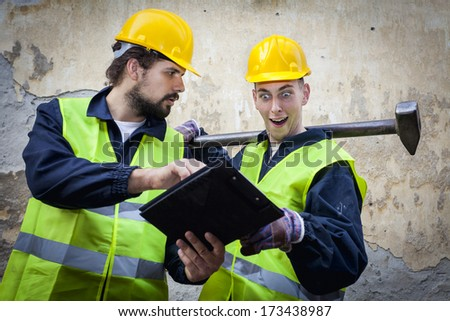 Two manual workers in protective suites, one holding paper and pen, showing the other one what he needs to do, the other one holding big hammer surprised face.