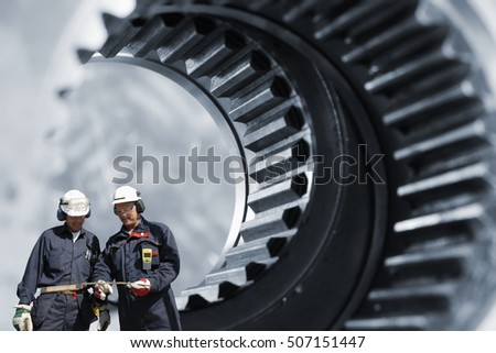 Two mechanics, workers in front of giant gears axle, as with steel industrial works