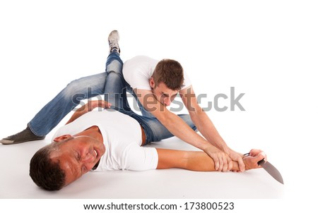 Two men fighting on the ground for a knife