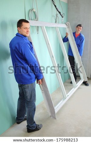 Two men in blue jackets holding a new window frame in an empty room