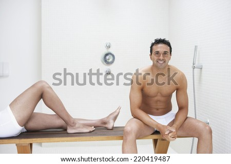 Two men in underwear on bench in bathroom