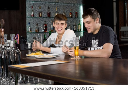 Two men relaxing together enjoying an evening at the pub sitting at the counter laughing over a glass of beer