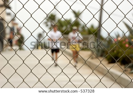 Two men running towards a chainlink fence. Shallow DOF, focus on fence.