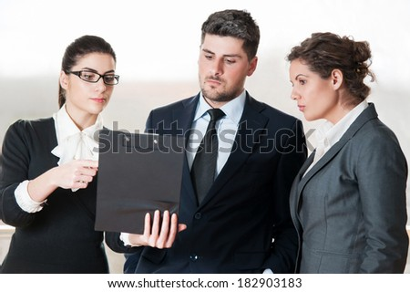 Two office colleagues and one business man talking over clipboard