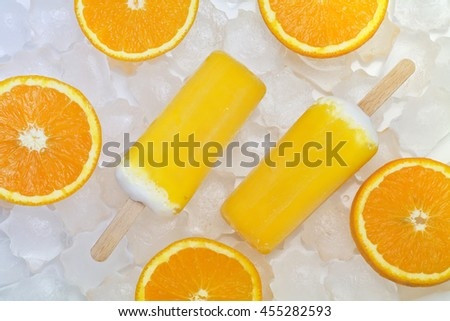 Two pcs of ice cream with orange slices on the pieces of ice.