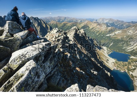 two people on a peak in a sunny autumn day