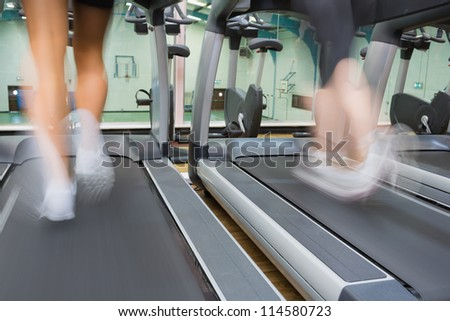 Two people running on treadmills side by side in the gym