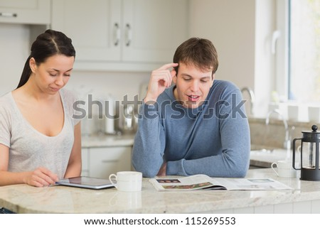 Two people sitting in a kitchen while they are talking and reading and drinking coffee