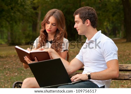 Two people solving business tasks in the park