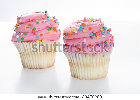 Two pink gourmet cupcake isolated on white