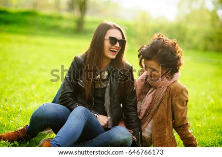 stock photo two pretty young women cheerfully spend time in the spring park girlfriends frolicking while 646766173