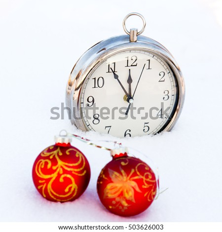 Two red christmas balls and watch on a snow. New Year greeting card concept.