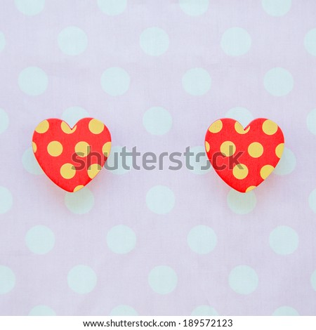 Two red heart with polka dot pink and white background