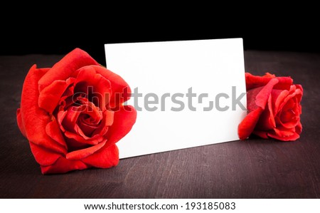 two red roses and blank gift card for text on old wood background, valentine day and love concept