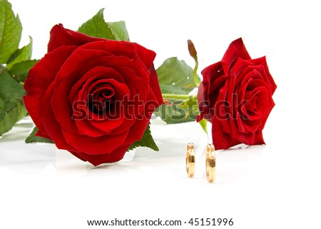 Two Red Roses And Wedding Rings Over White Background