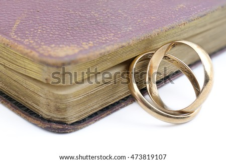 two rings forming a heart and an old book on white background