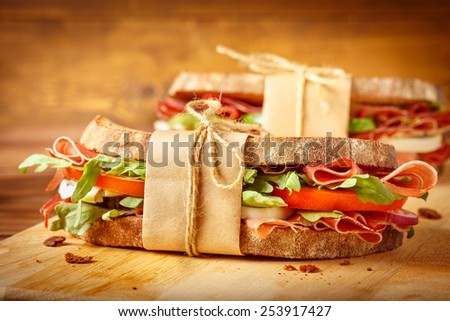 Two sandwiches with bacon and fresh vegetables on vintage wooden cutting board.Close-up.