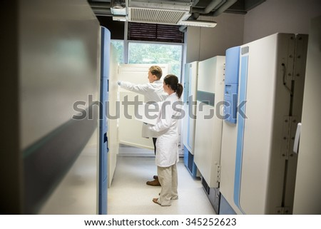 Two scientists using large fridge unit in the lab