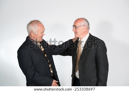 two senior businessmen friends smiling and shaking hands and shoulders