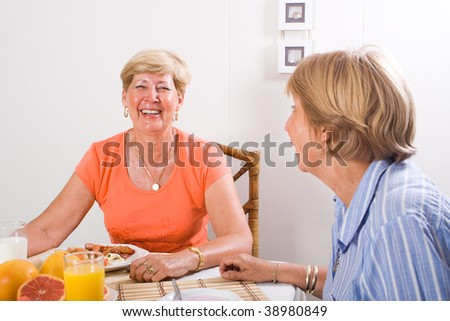 two senior sister having breakfast together