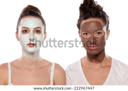 two serious young women with masks posing on white