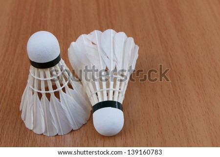 Two shuttlecock on wooden background
