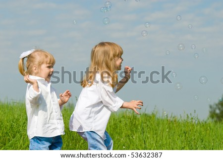 Two sisters are played with soap bubbles on rest