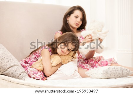 Two sisters playing with teddy bear while sitting on couch