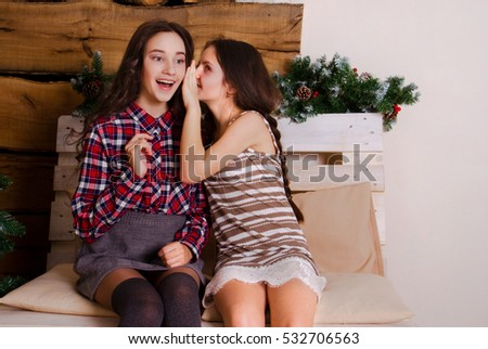 Two sisters share secrets, the girl tells a secret in the ear of his sister, girlfriend
